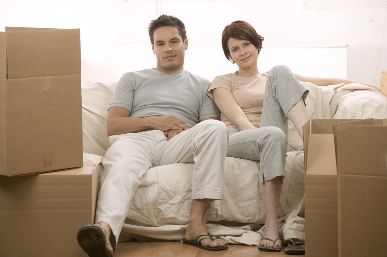 Couple Sitting on Couch with Moving Boxes